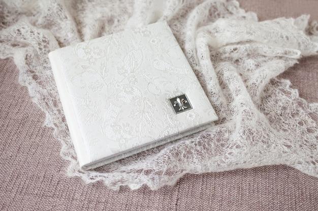 Fotobuch mit einem umschlag aus echtem leder. weiße farbe mit dekorativer prägung. weicher fokus.