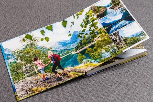 Fotobuchalbum auf decktisch mit reisefotos