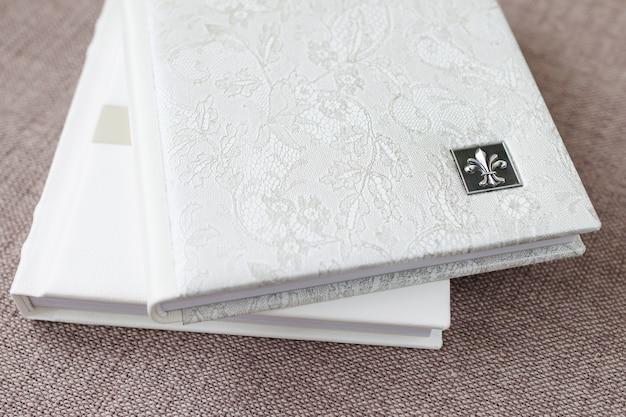 Fotobücher mit einem umschlag aus echtem leder. weiße farbe mit dekorativer prägung. weicher fokus.