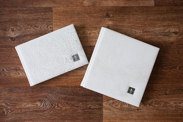 Fotobücher mit einem umschlag aus echtem leder. weiße farbe mit dekorativer prägung