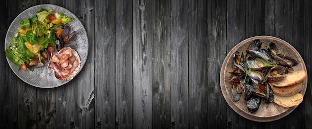 Fotocollage, zwei teller mit meeresfrüchten, auf einem grauen holzbretthintergrund. jakobsmuscheln, muscheln, tintenfisch, garnelen mit salat, orangenschnitzen und ananasscheiben. horizontale draufsicht