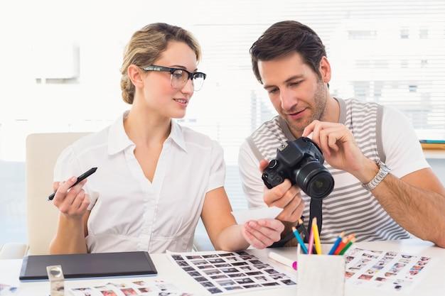 Fotoeditoren, die kamera in ihrem büro betrachten