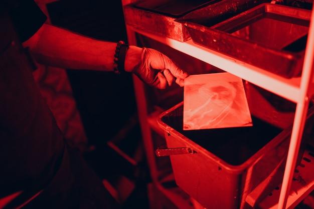 Fotoentwicklung. dunkelkammer, ambrotyp. rotlicht.