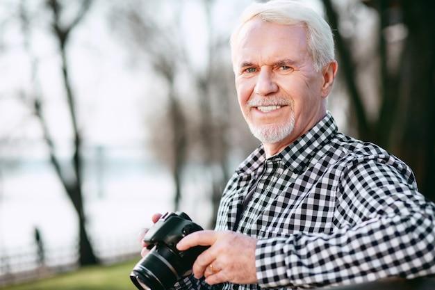 Fotofähigkeiten. ansprechender reifer mann, der kamera benutzt und kamera anstarrt