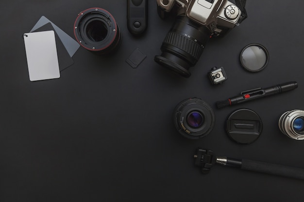 Fotograf arbeitsplatz mit dslr-kamerasystem, kamera-reinigungsset, objektiv und kamera-zubehör auf dunkelschwarzem tischhintergrund.