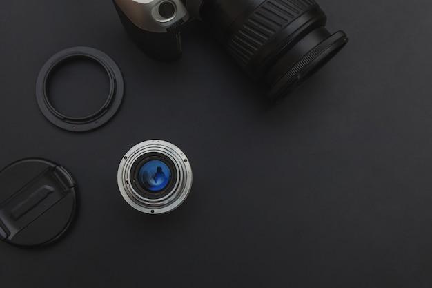 Fotograf arbeitsplatz mit dslr-kamerasystem und objektiv auf dunkelschwarzem tischhintergrund. hobby reisefotografie konzept. kopierraum für flach gelegte draufsicht.