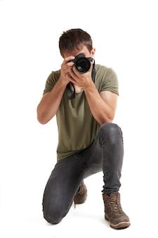 Fotograf auf einem knie auf dem boden, der ein foto macht. er trägt ein grünes hemd, graue hosen und braune stiefel.