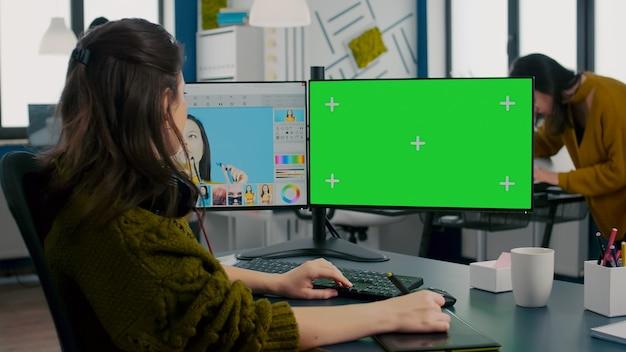 Fotograf, der an einem computer mit grünem mockup-bildschirm arbeitet