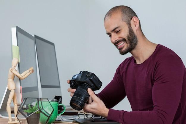 Fotograf, der aufgenommene fotos in seiner dslr-kamera überprüft