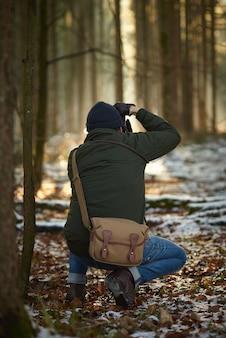 Fotograf, der bilder in einem wald macht, umgeben von grün, das mit schnee und blättern bedeckt ist