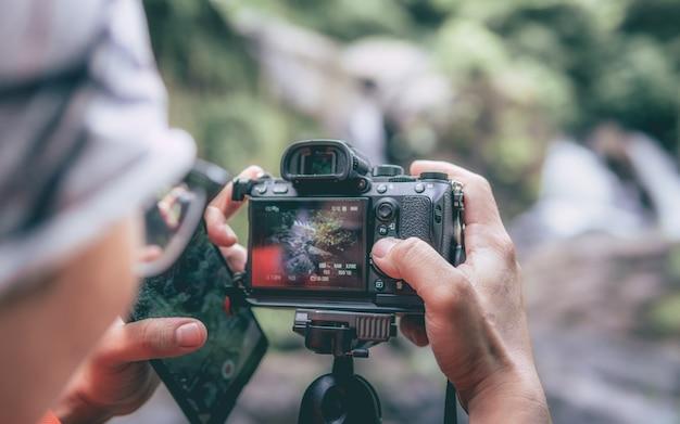 Fotograf, der digitalkamera einstellt
