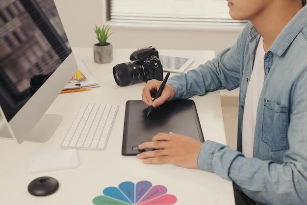 Fotograf, der ein bild auf einem laptop zeichnet und retuschiert, mit einem digitalen tablet und einem eingabestift. nahaufnahme der hand des mannes mit dslr-kamera im hintergrund. platz im vordergrund kopieren