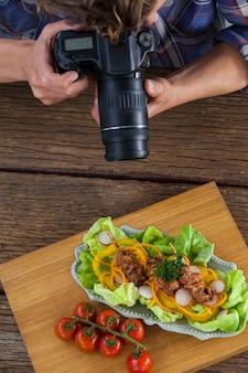 Fotograf, der ein bild von lebensmitteln mit digitalkamera klickt