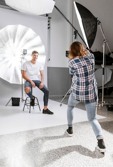Fotograf, der ein foto des männlichen modells im studio macht