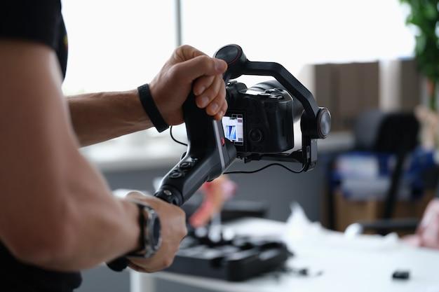 Fotograf, der ein video mit der kamera vom stativ in nahaufnahme aufnimmt