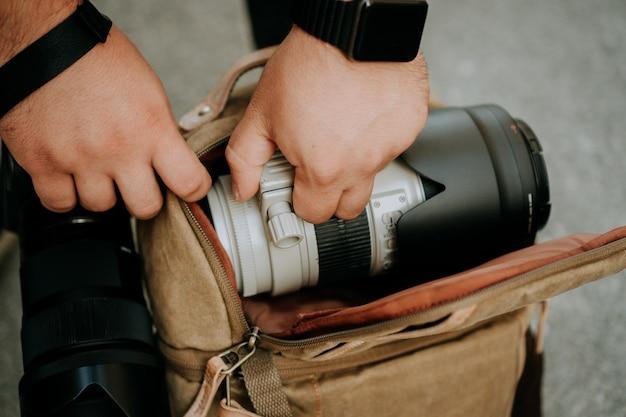 Fotograf, der ein weißes kameraobjektiv aus einer kameratasche herauszieht