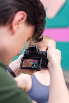 Fotograf, der eine junge blonde frau in sportbekleidung beim training im freien, mehrfarbigen hintergrund aufnimmt