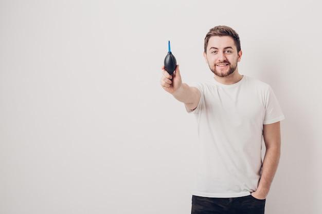 Fotograf, der eine vakuumpumpe für die reinigung der kamera hält. fokus auf luft b