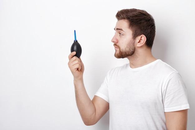 Fotograf, der eine vakuumpumpe für die reinigung der kamera hält. luftgebläse pu