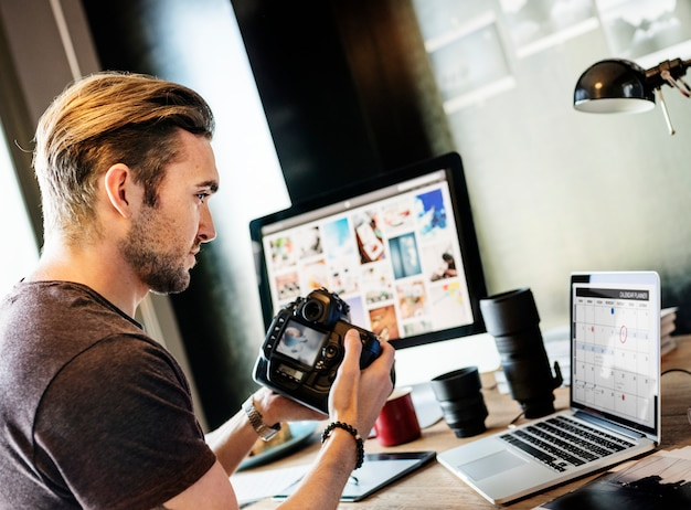 Fotograf, der foto-konzept überprüfend arbeitet