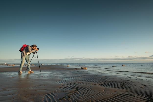 Fotograf, der foto macht, das mit einem stativ am strand steht