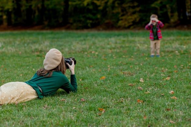 Fotograf der frau, die das kind fotografiert, um draußen im park zu verbringen