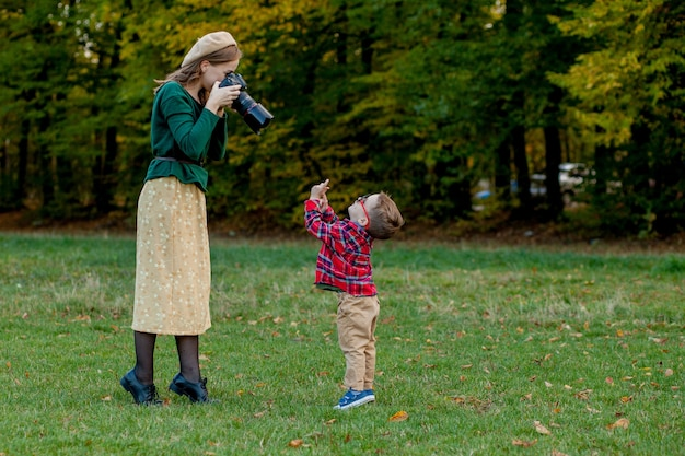 Fotograf der frau, die das kind fotografiert, um draußen im park zu verbringen.