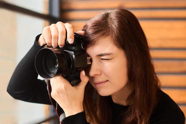 Fotograf der frau, die foto mit kamera auf professionellem fotoshooting mit tageslicht nahe fenster nimmt