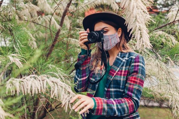 Fotograf der frau, die fotos mit kamera im sommergarten tragend maske nimmt. freiberufler, der im park arbeitet, der blühende büsche filmt