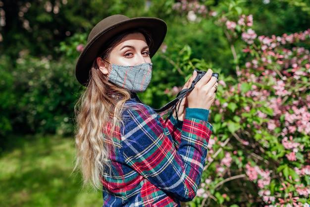 Fotograf der frau, die fotos unter verwendung der kamera im sommergarten tragend schutzmaske macht. freiberufler, der im park geht, der blumen blüht, die büsche blühen