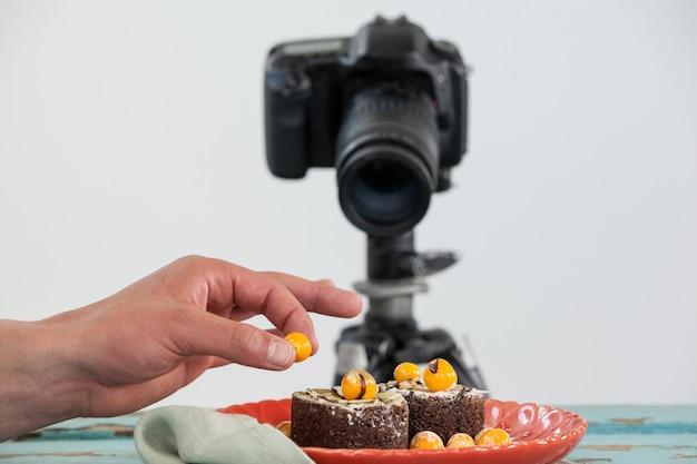Fotograf, der gelbe kirsche auf nachtisch, kamera im hintergrund hält