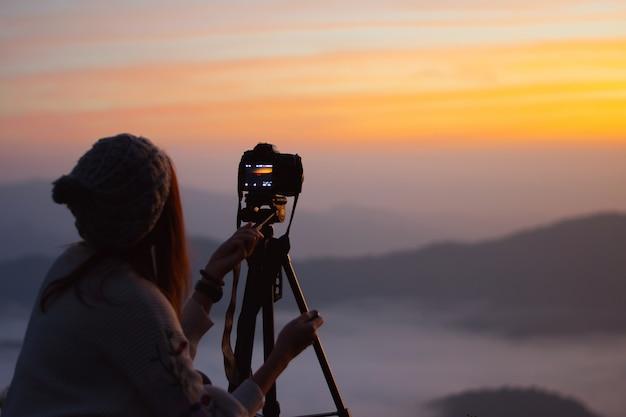 Fotograf der jungen frau, der foto der landschaft bei sonnenaufgang an der bergspitze macht.