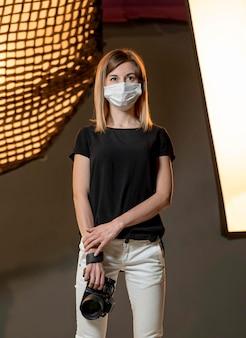 Fotograf, der medizinische maske in einem studio trägt