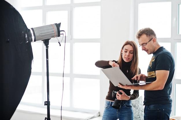 Fotograf, der seinem assistenten im studio über den schuss erklärt und auf laptop schaut. teamwork und brainstorming.