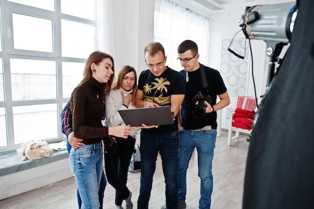 Fotograf, der seinem team im studio über den schuss erklärt und auf laptop schaut. gespräch mit seinen assistenten, die während eines fotoshootings eine kamera in der hand halten. teamwork und brainstorming.