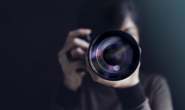 Fotograf, der selbstporträt nimmt. frau, die kamera verwendet, um foto zu machen. dunkler ton, vorderansicht. selektiver fokus auf linse. direkt in eine kamera