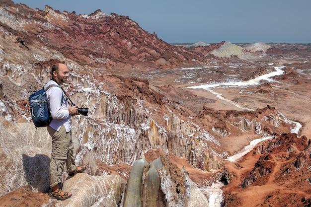 Fotograf, der zu fuß auf salzberge in hormuz island, hormozgan, iran wandert.