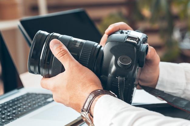 Fotograf des jungen mannes, der an einem computer arbeitet. schreibtisch mit tastatur, kamera, laptop und objektiven.