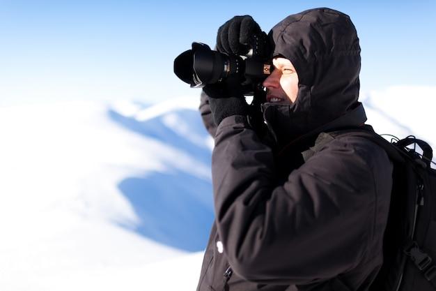 Fotograf des jungen mannes in der winterkleidung stehend und foto im sonnenlicht machend