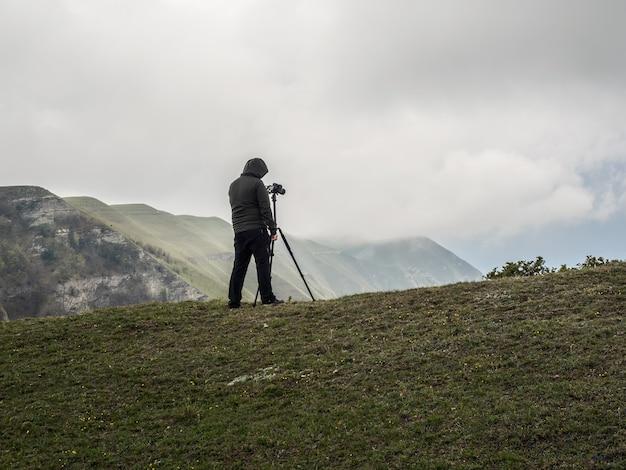 Fotograf fotografiert eine landschaft mit einem stativ, während er bei schwierigen wetterbedingungen am rand einer klippe steht.