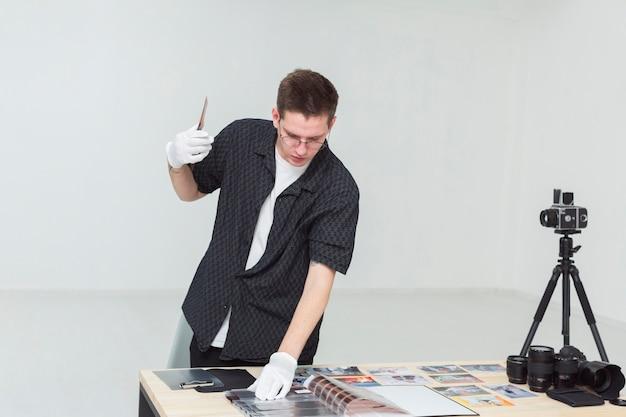 Fotograf in einem studio, das albumfoto betrachtet