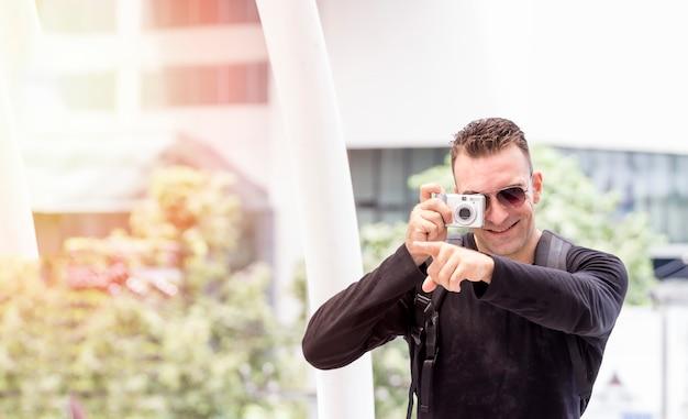 Fotograf lifestyle concept; fotograf mit kamera fühlt sich glücklich, macht spaß um ci zu reisen