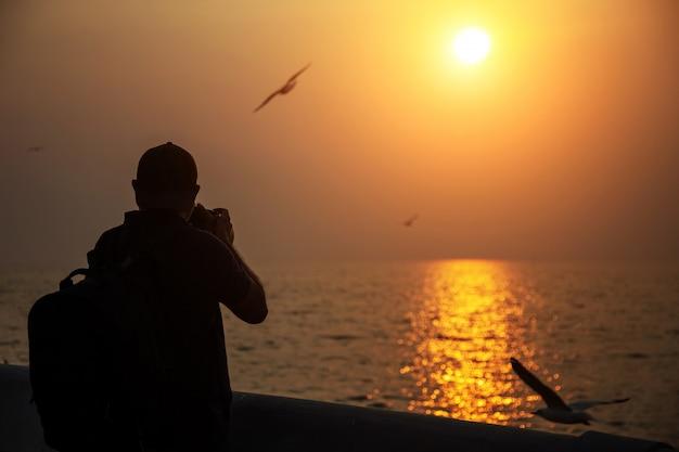 Fotograf machen sonnenuntergangfoto am dock und am meerblick