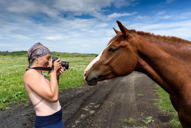 Fotograf macht fotos von pferd auf dem feld