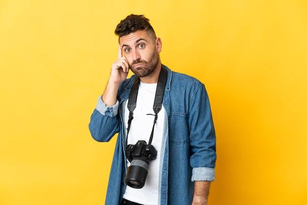 Fotograf mann auf gelbem hintergrund isoliert denken eine idee