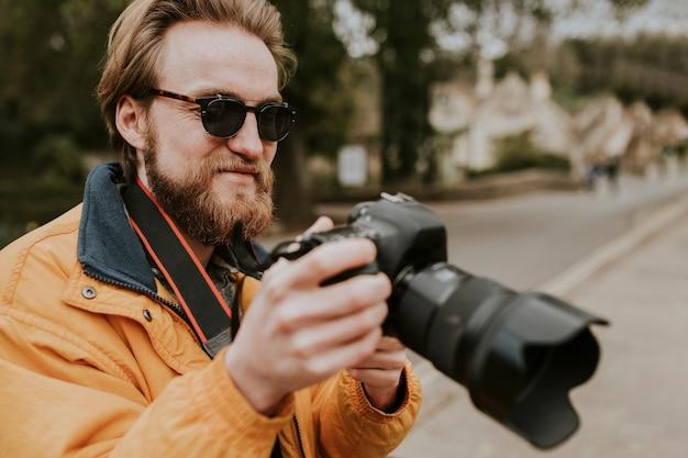 Fotograf mann, der seine fotos auf der kamera ansieht