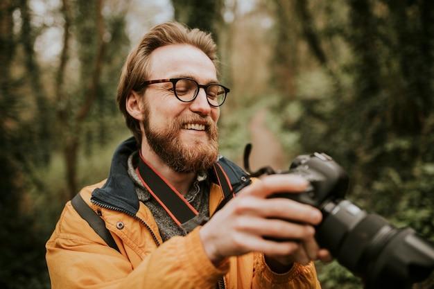 Fotograf mann, der seine fotos auf der kamera im freien betrachtet