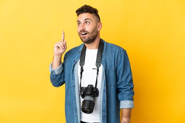 Fotograf mann isoliert auf gelbe wand denken eine idee, die den finger nach oben zeigt