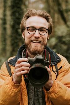 Fotograf mann lächelt, während er die kamera im wald hält