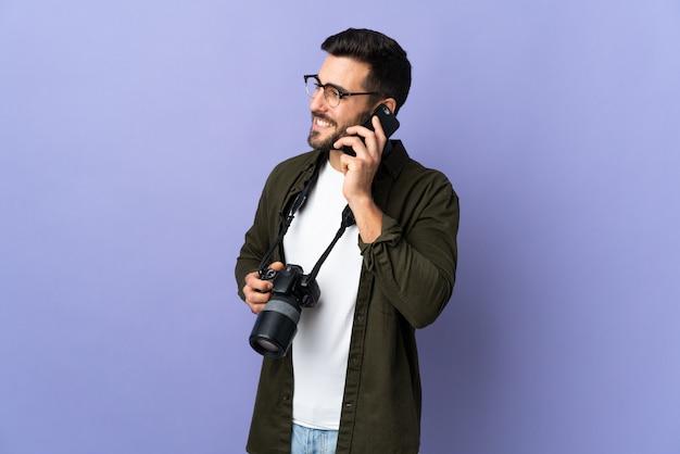 Fotograf mann über isolierte lila wand, die ein gespräch mit dem handy mit jemandem hält